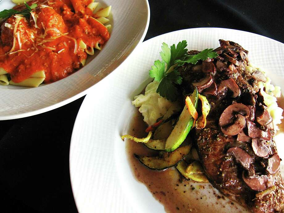 Grilled rib-eye steak with garlic mashed potatoes, roasted vegetables and a mushroom-wine demi-glace, foreground, and penne pasta with meat sauce and meatballs from Pesto Ristorante. Photo: Mike Sutter /San Antonio Express-News