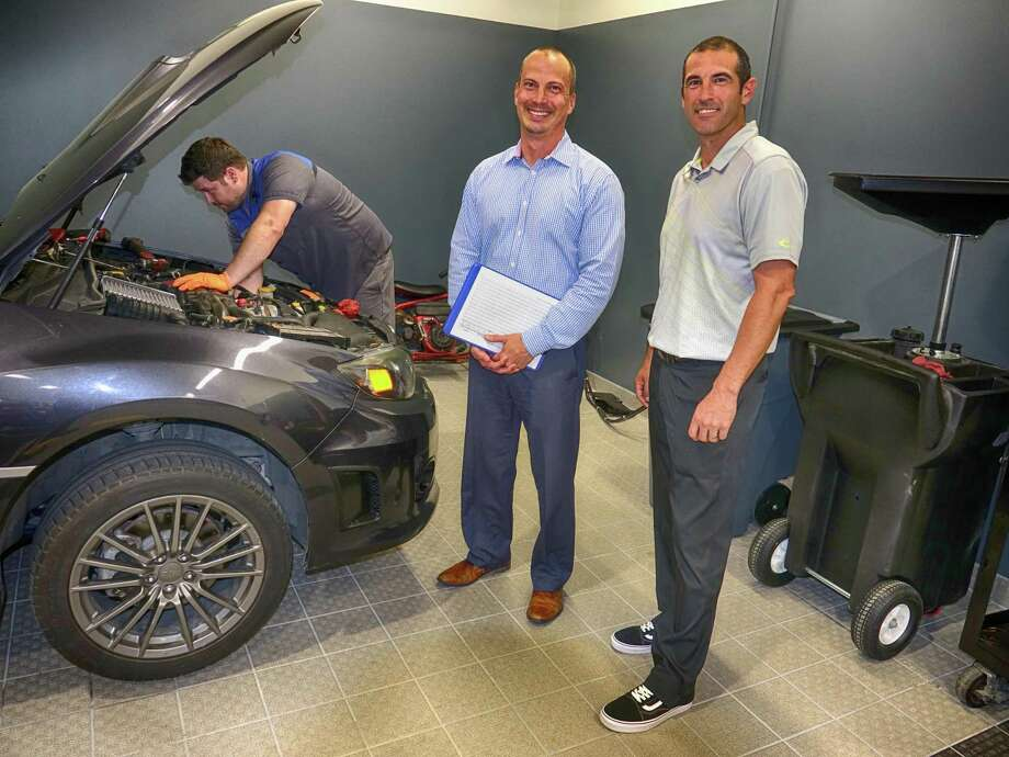 Service director Wally Mendez (with clipboard), general manager Chris Martin and technician Eric Williams, under the hood, in Superior Subaru's air-conditioned and heated enclosed shop. Photo: Jeff Yip / Jeff Yip
