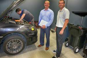 Service director Wally Mendez (with clipboard), general manager Chris Martin and technician Eric Williams, under the hood, in Superior Subaru's air-conditioned and heated enclosed shop.