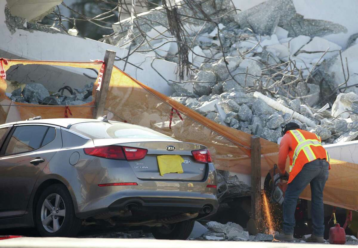 A worker uses a saw next to a crushed car under a section of a collapsed pedestrian bridge on March 16 near Florida International University in the Miami area. The new pedestrian bridge that was under construction collapsed onto a busy Miami highway on March 15, crushing vehicles beneath massive slabs of concrete and steel, killing and injuring several people, authorities said.