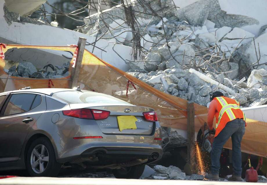 A worker uses a saw next to a crushed car under a section of a collapsed pedestrian bridge on March 16 near Florida International University in the Miami area. The new pedestrian bridge that was under construction collapsed onto a busy Miami highway on March 15, crushing vehicles beneath massive slabs of concrete and steel, killing and injuring several people, authorities said. Photo: Wilfredo Lee, STF / Associated Press / Copyright 2018 The Associated Press. All rights reserved.