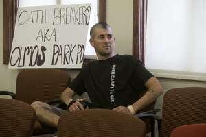 David Nunez sits with a sign Thursday at Olmos Park City Hall while the Olmos Park City Council meets in executive session to discuss an ordinance prohibiting people other than police from carrying long guns in public, a conflict with state law. The council repealed the ordinance.