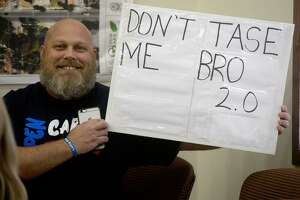 Greg Holland sits with a sign Thursday at Olmos Park City Hall while the City Council meets in executive session to discuss its ordinance prohibiting people other than police from carrying long guns in public, a conflict with state law.