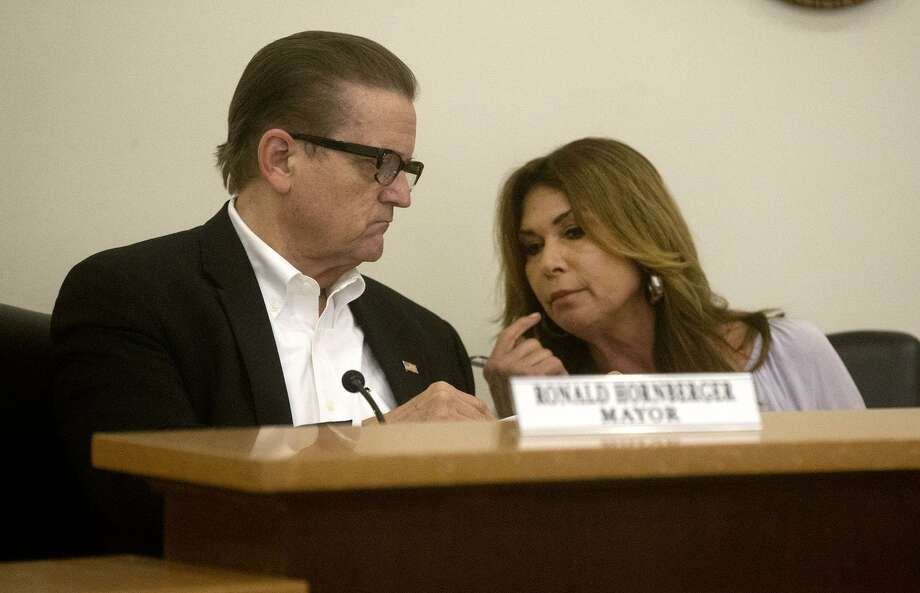Olmos Park Mayor Ronald Hornberger speaks with Council member Sharon Plant on Thursday before the Olmos Park City Council met in executive session to its ordinance prohibiting people other than police from carrying long guns in public, a conflict with state law. Photo: John Davenport /San Antonio Express-News / ©John Davenport/San Antonio Express-News