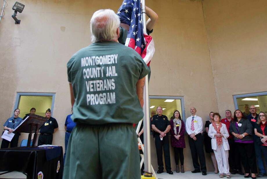 Inmates with the Pod 7 Veterans Program raise the flag during a small ceremony in honor of Vietnam Veteran's Day inside the Montgomery County Jail, Thursday, March 29, 2018, in Conroe. The pod includes wrap-around services and is centered on helping the veteran inmates assimilate back into civilian life. Photo: Jason Fochtman, Staff Photographer / © 2018 Houston Chronicle