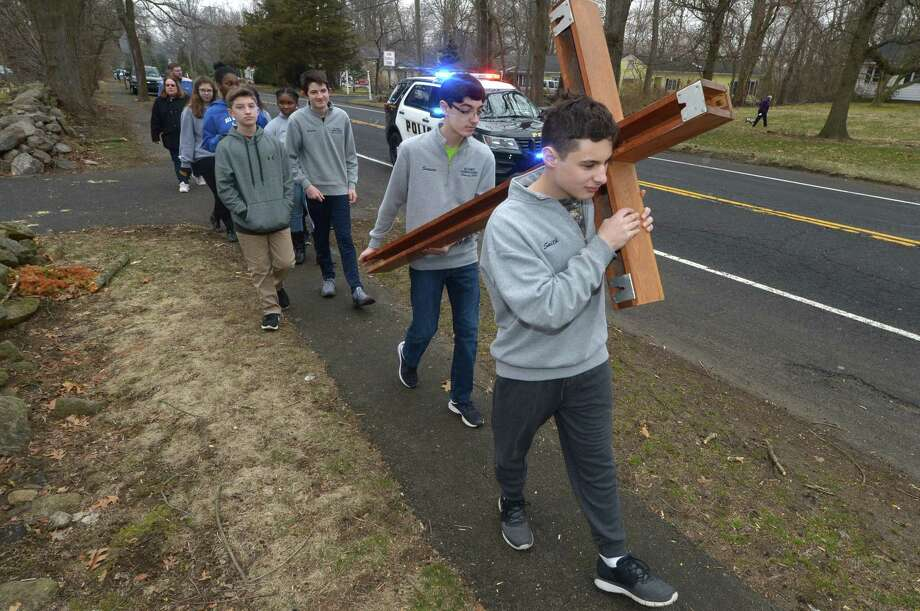 Six All saints Catholic School 8th grade students including Erik Swanson and Jack Smith proceed with a cross down West Rocks Road and to the school Thursday, March 29, 2018, for Holy Thursday services at the school in Norwalk, Conn. The student body recited the Sorrowful Mysteries of the Rosary during the assembly in the auditorium in recognition of Good Friday. Photo: Erik Trautmann / Hearst Connecticut Media / Norwalk Hour