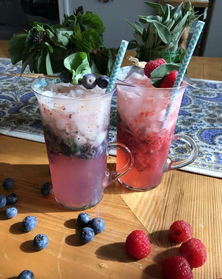 Blueberry-basil Mojito cocktail, left, and Raspberry-sage Mojito Photo: Emily Spicer / San Antonio Express-News