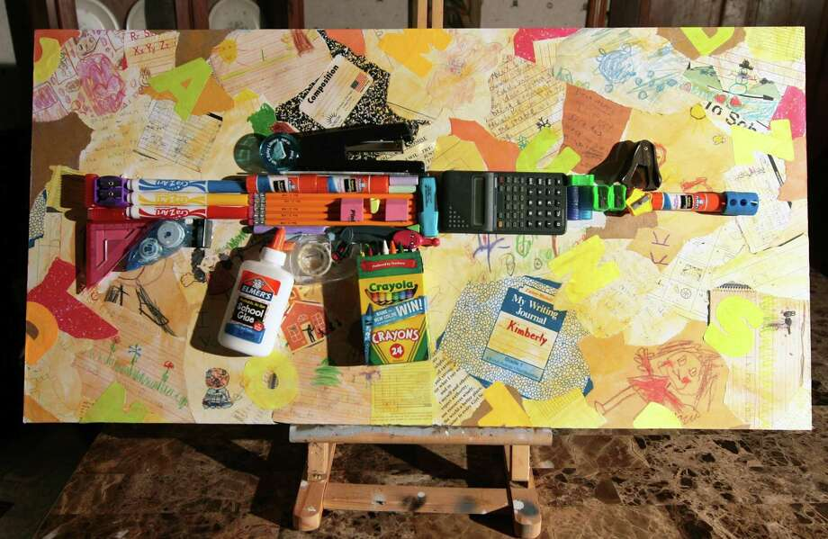 A view of a 3-D collage created by Paier art student Kim Krivensky, using school supplies to depict an AR-15 atop her school work from elementary and high school days, on display at her home in Oxford, Conn., Mar. 27, 2018. Photo: Christian Abraham / Hearst Connecticut Media / Connecticut Post