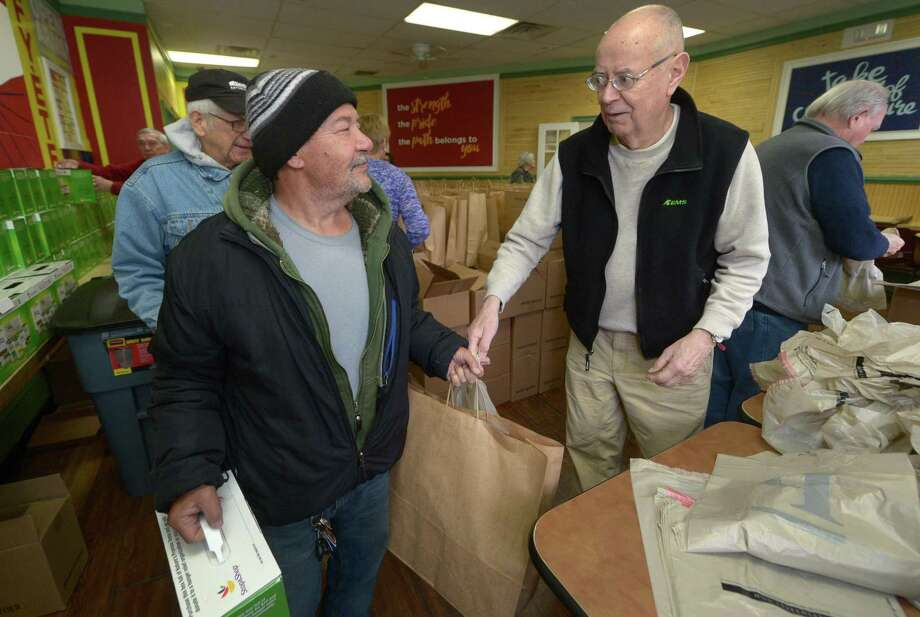 Volunteers from the First Congregational Church in Darien including Marke Thorne, right, put together bags of food for Easter and distribute them to those in need like Felix Serrano, at the Open Door Shelter in Norwalk on Thursday. Photo: Erik Trautmann / Hearst Connecticut Media / Norwalk Hour