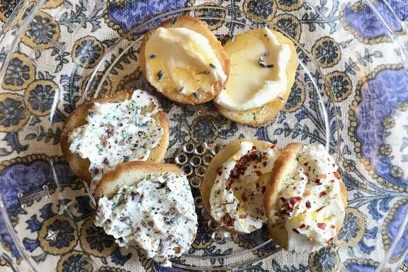 Clockwise from bottom left: Kalamata olive-tarragon ricotta toast, honey-lavender ricotta toast, olive oil-red pepper flakes ricotta toast.
