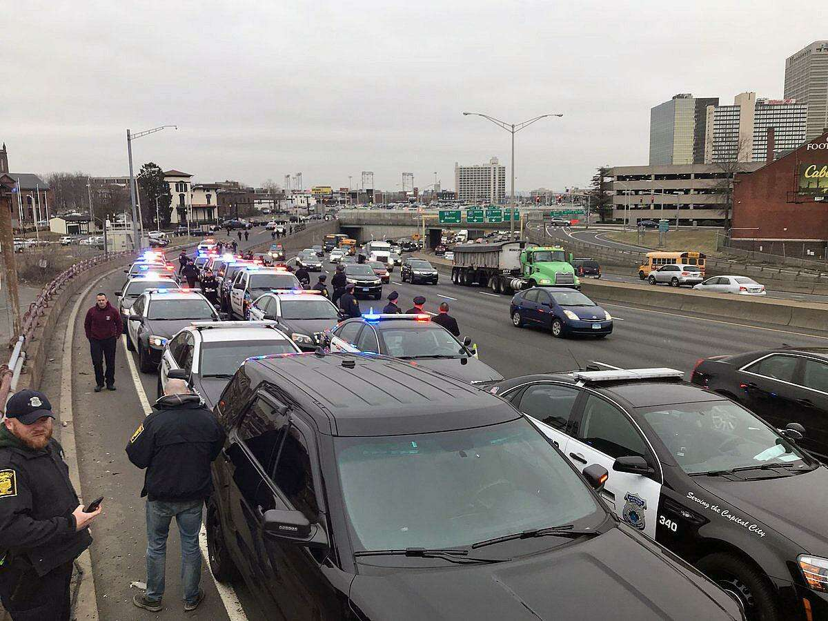 A fleet of Hartford police officers waiting on the highway on March 29, 2018. The officers are waiting for the procession escorting fallen Trooper First Class Kevin M. Miller to the Medical Examiner's office in Farmington. Miller died Thursday from injuries sustained during a crash in Tolland, Conn., on the highway while he was on duty.