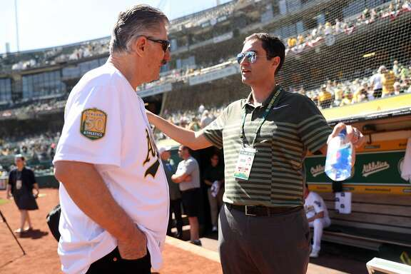 Oakland Athletics' President Dave Kavel chats with Hall of Famer Rollie Fingers before A's play Los Angeles Angels in season opening game at Oakland Coliseum in Oakland, Calif., on Thursday, March 29, 2018.