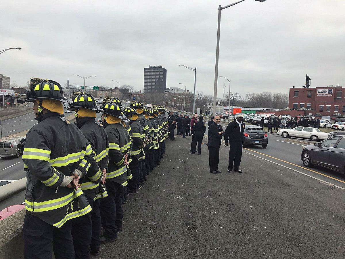 A fleet of Hartford police officers and firefighters waiting on the shoulder of Interstate 84 in Hartford, Conn., on March 29, 2018. The officers are waiting to join the procession, escorting fallen Trooper First Class Kevin M. Miller to the Medical Examiner's office in Farmington. Miller died Thursday from injuries sustained during a crash on the highway while he was on duty.
