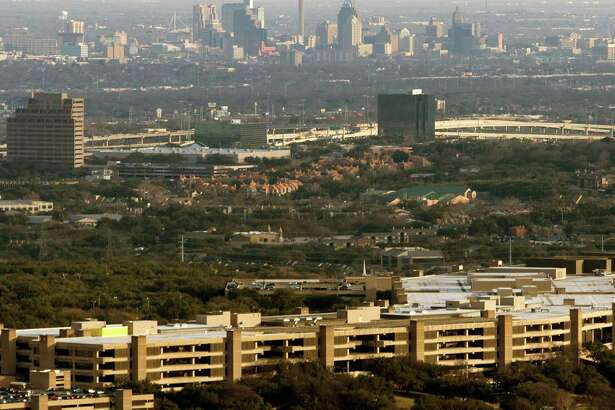 "Most of USAA's employees will continue to work from home through until Sept. 1, though about 1,000 across its four campuses will begin to return to the office next month under a ""pilot program."" Pictured is the USAA headquarters building, with downtown San Antonio in the background, as seen in a 2018 aerial photo."