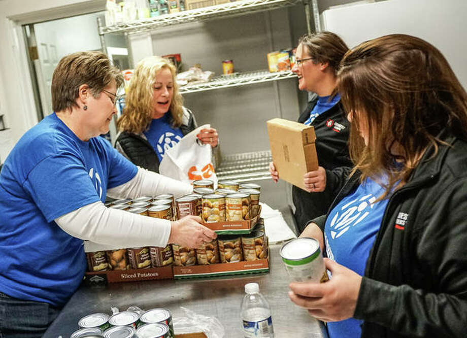 Midwest Members Credit Union employees work Saturday to package food for needy families ahead of the Easter holiday. Photo: Nathan Woodside | For The Telegraph