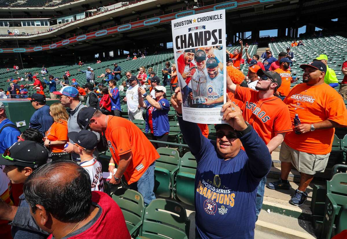 ARLINGTON, TX - MARCH 29: A Houston Astros fan holds up a newspaper cover with a photo from the World Series as the team starts batting practice before the Opening Day game agaisnt the Texas Rangers at Globe Life Park in Arlington on March 29, 2018 in Arlington, Texas. (Photo by Richard Rodriguez/Getty Images)