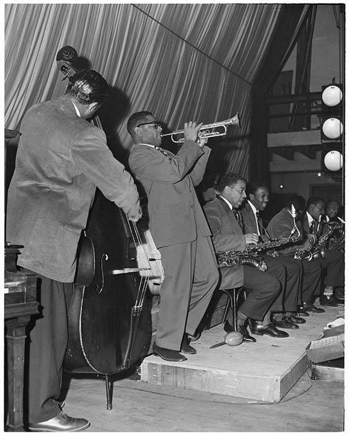 On February 19, 1949, trumpeter Dizzy Gillespie and his orchestra played at Seattle's Senator Ballroom. Here, Gillespie plays, accompanied by bass and the rest of the orchestra. His big band bebop style was new to Seattle musicians. Courtesy of MOHAI, Al Smith Collection, 2014.49.002-011-0034