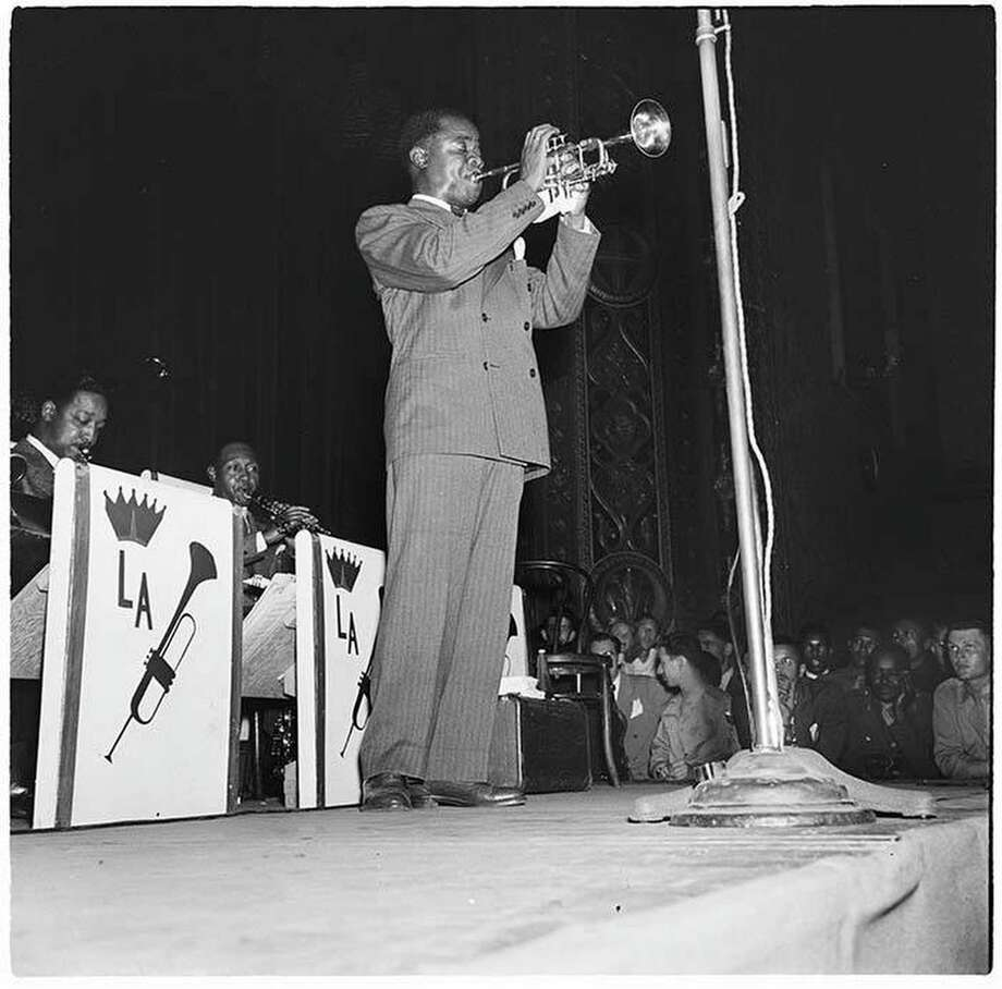 Trumpet player Louis Armstrong and his band played Seattle's Civic Auditorium on July 17 and 18, 1944. Many of his fans at the edge of the stage are in the military.  Courtesy of MOHAI, Al Smith Collection, 2014.49.002-027-0094 Photo: Al Smith, MOHAI, Al Smith Collection, 2014.49.002-027-0094 / Copyright Museum of History & Industry