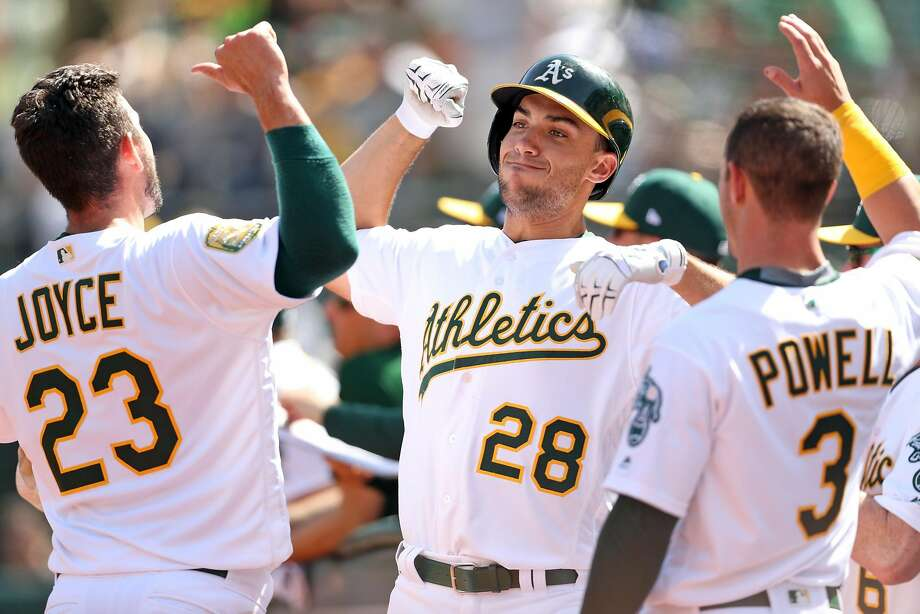 Oakland Athletics' Matt Olson celebrates his solo home run with Matt Joyce n 5th inning against Los Angeles Angels during MLB game at Oakland Coliseum in Oakland, Calif., on Thursday, March 29, 2018. Photo: Scott Strazzante / The Chronicle