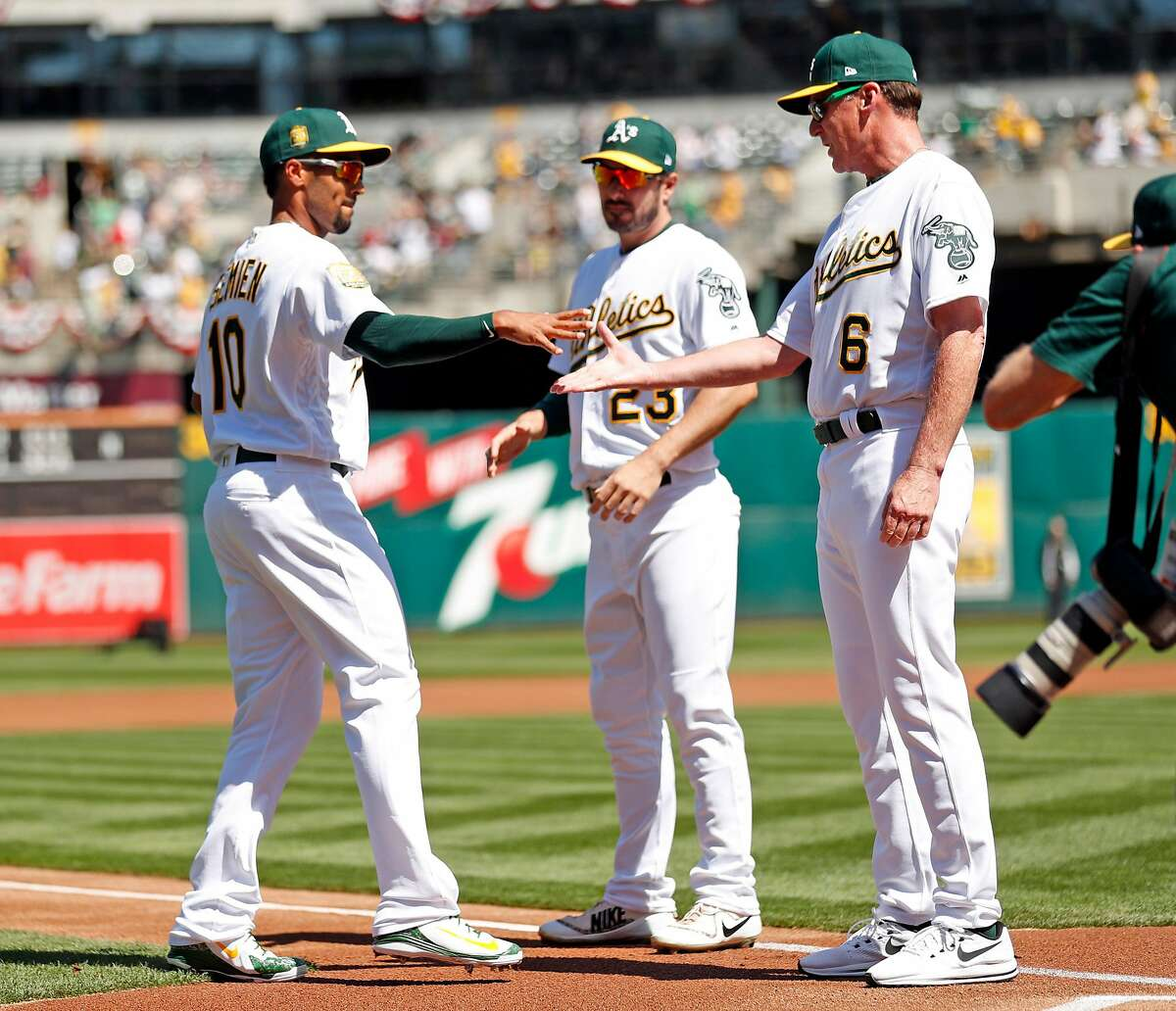 Oakland Athletics' manager Bob Melvin greets Marcus Semien before A's home opener against Los Angeles Angels at Oakland Coliseum in Oakland, Calif., on Thursday, March 29, 2018.