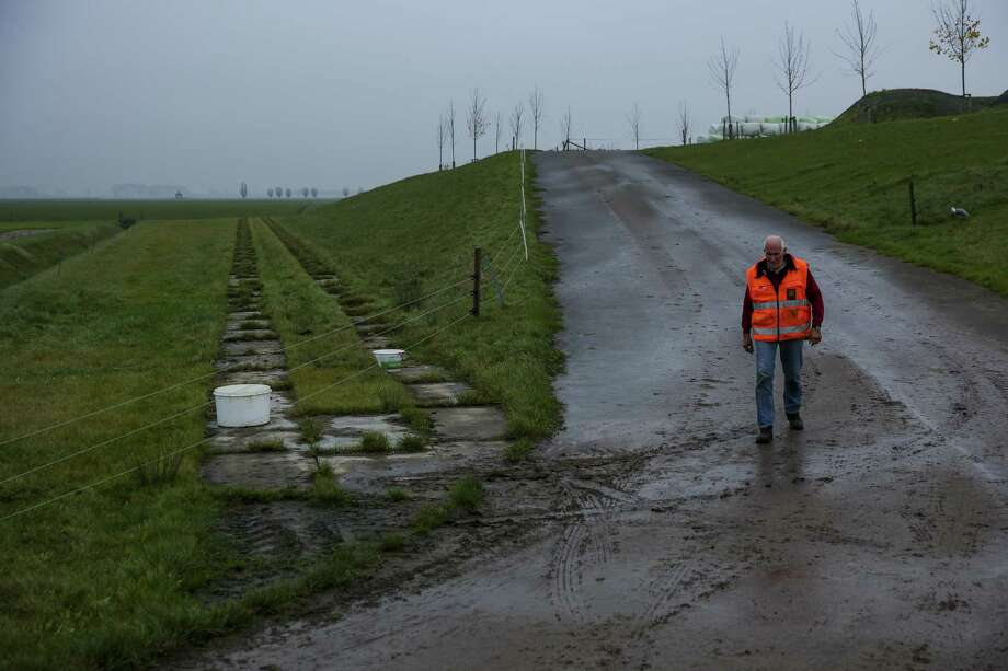 A farmer in Overdiepse Polder, walks down to his farmland from the raised piece of land where his barn and home are built. The dikes in the area have been lowered to allow rivers to flood farmland if necessary to protect areas downstream Wednesday, Nov. 15, 2017 in Waspik, the Netherlands. Photo: Michael Ciaglo, Houston Chronicle / Houston Chronicle / Michael Ciaglo