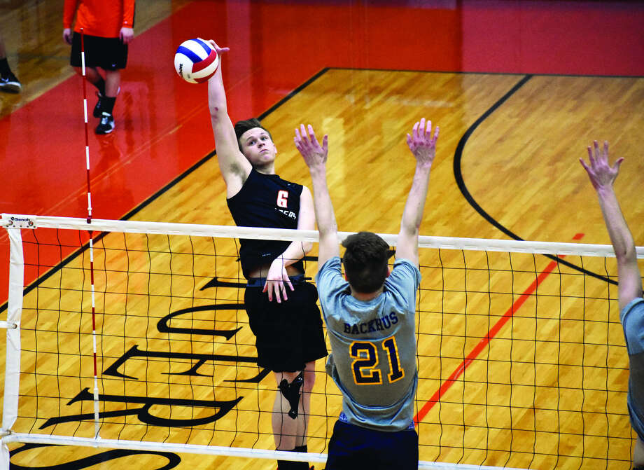 Edwardsville's Evan Billiter, left, smashes down a kill during the first game of a Southwestern Conference match against the O'Fallon Panthers inside the Lucco-Jackson Gymnasium.