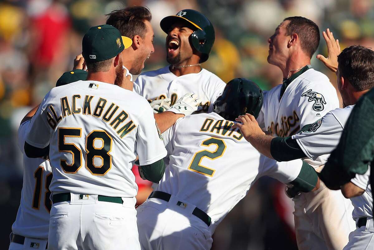 Oakland Athletics' Marcus Semien celebrates his game-winning RBI during A's 6-5 win over Los Angeles Angels in 11 innings in MLB game at Oakland Coliseum in Oakland, Calif., on Thursday, March 29, 2018.