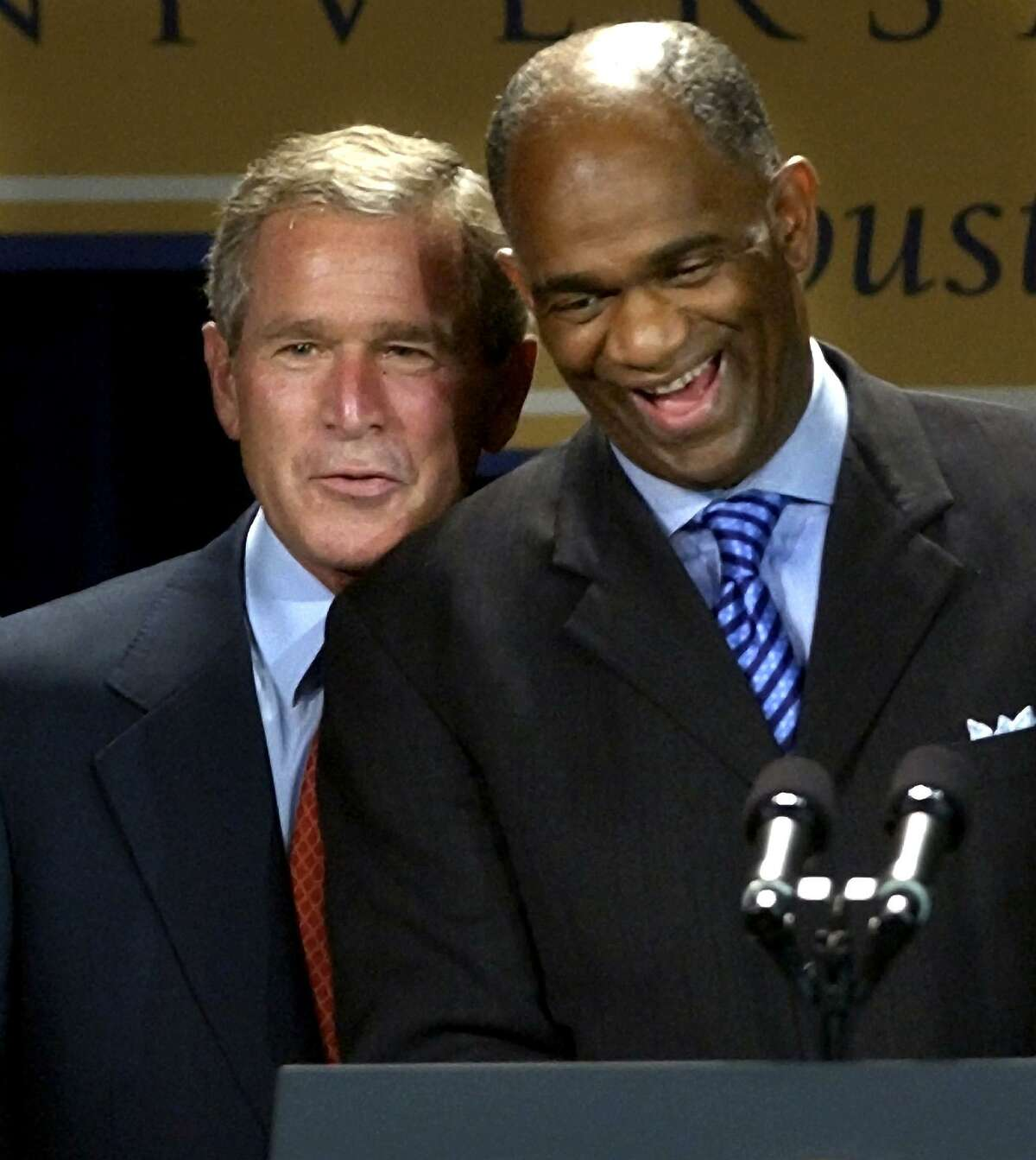 President George W. Bush, left, shares a laugh with Pastor Kirbyjon Caldwell as they are introduced during a fundraiser for the Power Center in Houston in September 2003. (AP Photo/David J. Phillip)