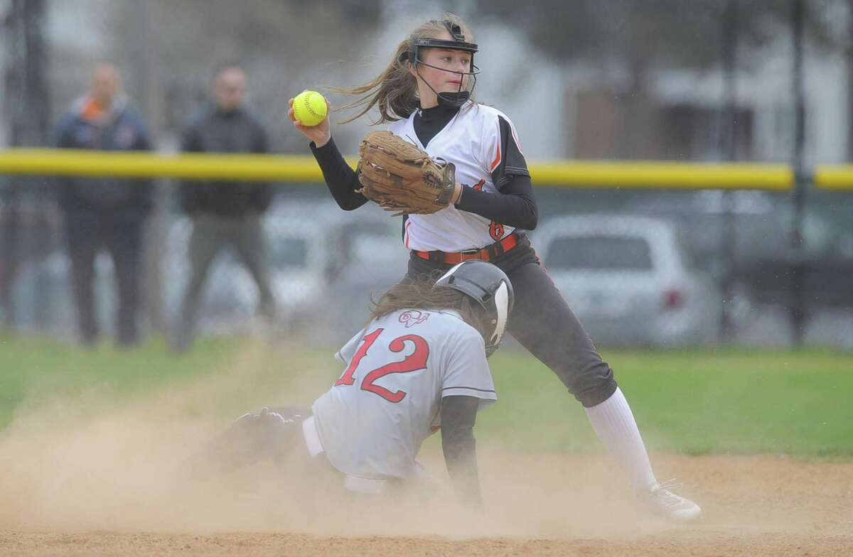 New Canaan's Kara Fahey is thrown out at second base as Stamford's Gloria Mattioli turns to throw to first in a varsity girls softball game at Stamford High School on April 19, 2017. Mattioli returns to lead the Black Knights.