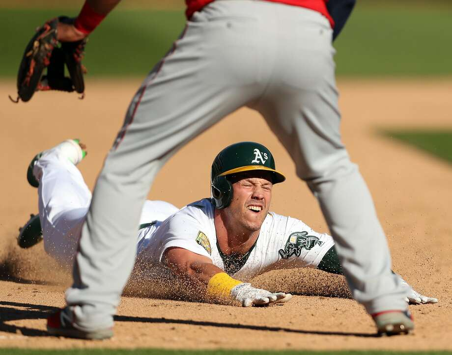 Setting up the game-winning run, Oakland Athletics' Boog Powell slides into third base with an 11th  inning triple against Los Angeles Angels during A's 6-5 extra-inning win in MLB game at Oakland Coliseum in Oakland, Calif., on Thursday, March 29, 2018. Photo: Scott Strazzante / The Chronicle
