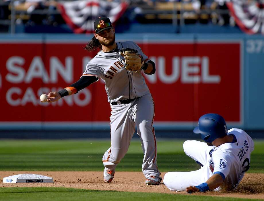 Brandon Crawford #35 of the San Francisco Giants turns a double play over Chris Taylor #3 of the Los Angeles Dodgers during the third innning on the 2018 Major League Baseball opening day at Dodger Stadium on March 29, 2018 in Los Angeles, California. Photo: Harry How / Getty Images