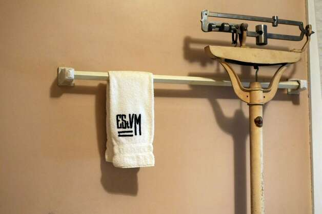Monogrammed towels hang in the bathroom, where an antique bathroom scale reads 96 pounds. ( Philip Kamrass / Times Union) Photo: PHILIP KAMRASS