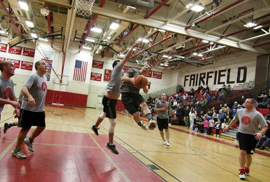 "Fairfield Police's Alex Fucci attempts a layup as Fairfield Fire's Finn MacDaniel defends during the Barnum Festival ""Battle of the Badges"" Basketball Fundraiser in Fairfield, Conn., on Thursday, Mar. 29, 2018. The tournament also has the Bridgeport Fire and Police department teams facing each other. The winner of each game then goes on to face each other for the final game. Photo: Christian Abraham / Hearst Connecticut Media / Connecticut Post"