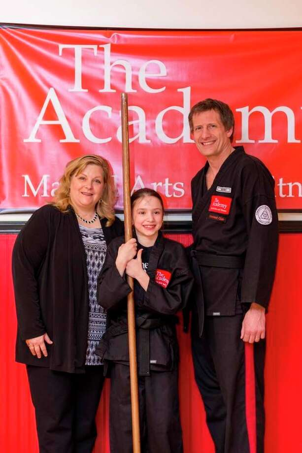 Addison Bennett (center) recently earned a black belt from The Academy Martial Arts and Fitness. She is flanked by Laura Sira and Craig Sira of The Academy.