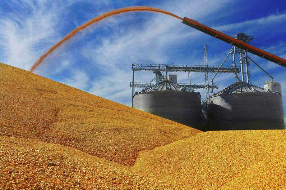 Illinois farmers deposit harvested corn on the ground outside a full grain elevator in Virginia, Ill. Photo: Seth Perlman, STF / Associated Press / Copyright 2017 The Associated Press. All rights reserved.