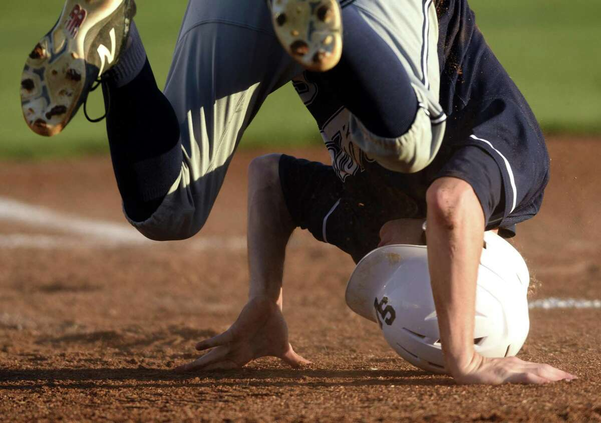 Smithson Valley's Shane Shepherd tumbles after scoring in the first inning during District 27-6A high school baseball action at Clemens High School on Thursday, March 29, 2018.