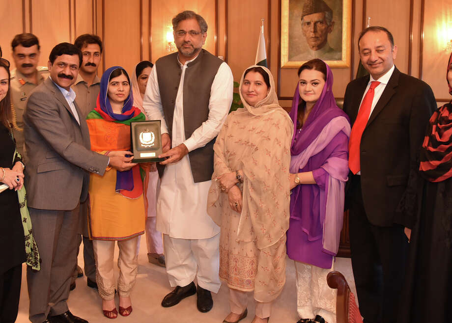 In this photo released by the Press Information Department, Pakistani Nobel Peace Prize winner Malala Yousafzai, second from left, receives a souvenir from Shahid Khaqan Abbasi, center, Prime Minister of Pakistan with her family members in Islamabad, Pakistan, Thursday, March 29, 2018. Yousafzai on Thursday said she was excited to be back in Pakistan for the first time since she was shot in 2012 by Taliban militants angered at her championing of education for girls. (Press Information Department, via AP) / Press Information Department