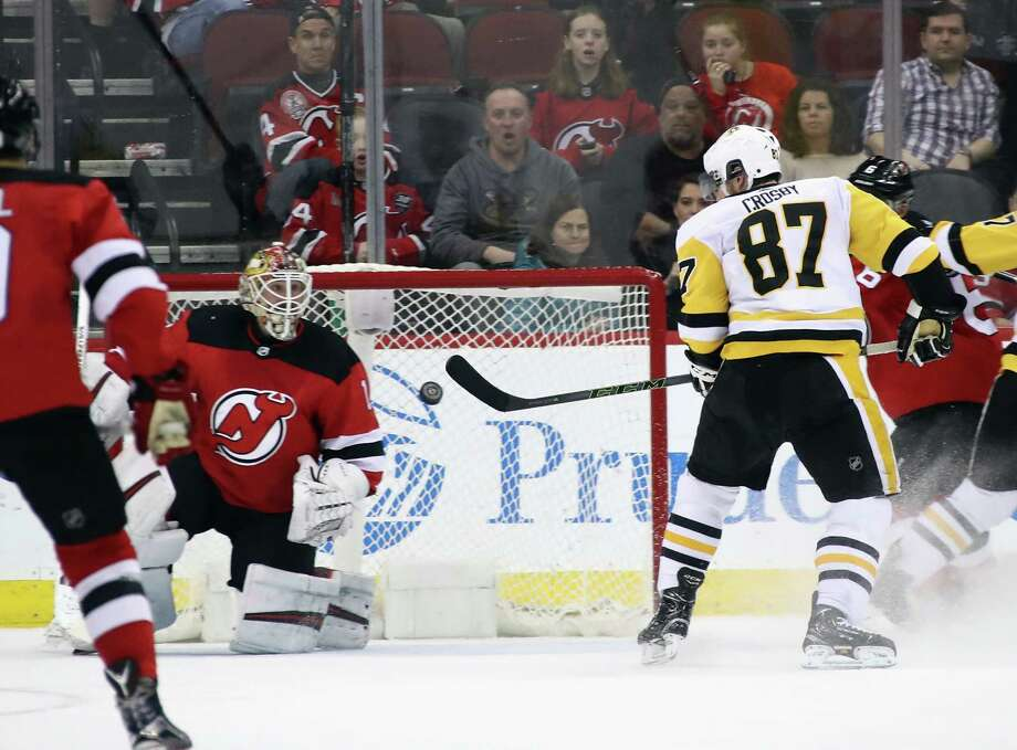 NEWARK, NJ - MARCH 29:  Sidney Crosby #87 of the Pittsburgh Penguins scores the game winning goal in overtime against Keith Kinkaid #1 of the New Jersey Devils at the Prudential Center on March 29, 2018 in Newark, New Jersey.  The Penguins defeated the Devils 4-3 in overtime.  (Photo by Bruce Bennett/Getty Images) Photo: Bruce Bennett / 2018 Getty Images