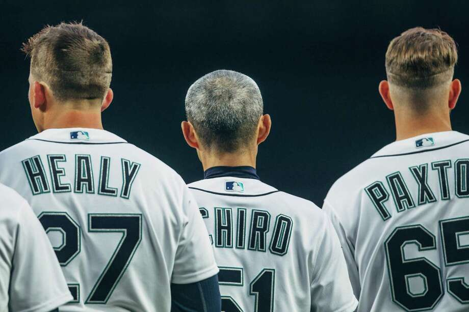 Mariners outfielder Ichiro Suzuki stands between first baseman Ryon Healy and pitcher James Paxton, during the national anthem on opening day 2018 at SafeCo Field on Thursday, March 29, 2018. Suzuki, 44, returned to the Mariners after playing for them for 12 years beginning in 2001. Photo: GRANT HINDSLEY, SEATTLEPI.COM / SEATTLEPI.COM