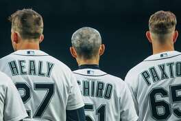 Mariners outfielder Ichiro Suzuki stands between first baseman Ryon Healy and pitcher James Paxton, during the national anthem on opening day 2018 at SafeCo Field on Thursday, March 29, 2018. Suzuki, 44, returned to the Mariners after playing for them for 12 years beginning in 2001.