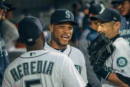 Robinson Cano jokes with Guillermo Heredia and Ichiro Suzuki in the dugout before their season opener against Cleveland at SafeCo Field on Thursday, March 29, 2018.(GRANT HINDSLEY, seattlepi.com)