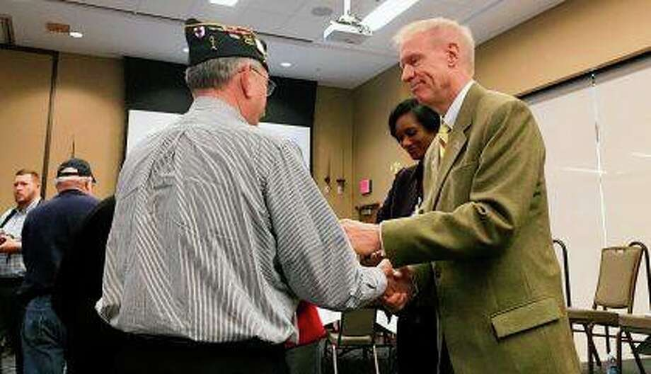 Gov. Bruce Rauner presents a Vietnam veteran with a lapel pin marking their service during a commemoration service for veterans of the war at the University of Illinois at Springfield on Thursday. Rauner presented lapel pins to dozens of Vietnam-era veterans who served from 1955 to 1975. Photo: John O'Connor | AP