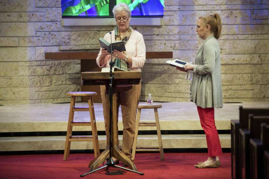 Sue Phipps, left, reads from the Bible as with Sara Wiggins awaits her turn in The Spoken Word Bible reading. Photo: Brett Coomer, Staff / Houston Chronicle / © 2018 Houston Chronicle