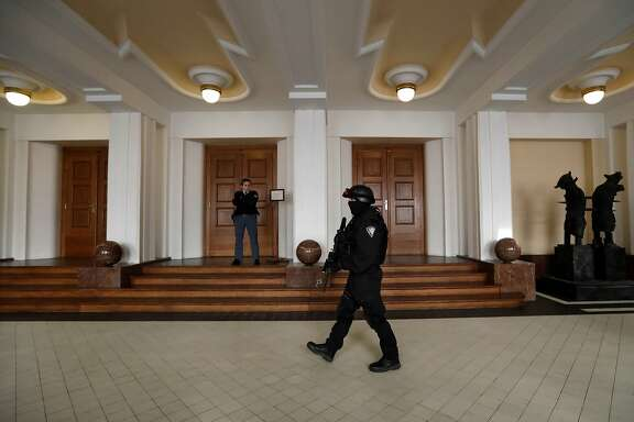 FILE - In this Friday, Nov. 24, 2017 file photo, a prison guard walks outside a courtroom during an appeal by Yevgeniy Nikulin from Russia who faces charges of hacking computers of American companies, in Prague, Czech Republic. The Czech Republic extradited a Russian man to the U.S. to face charges of hacking computers at LinkedIn, Dropbox and other American companies, an official said Friday March 30, 2018. Yevgeniy Nikulin was flown to the U.S. overnight, Justice Ministry spokeswoman Tereza Schejbalova said. (AP Photo/Petr David Josek)