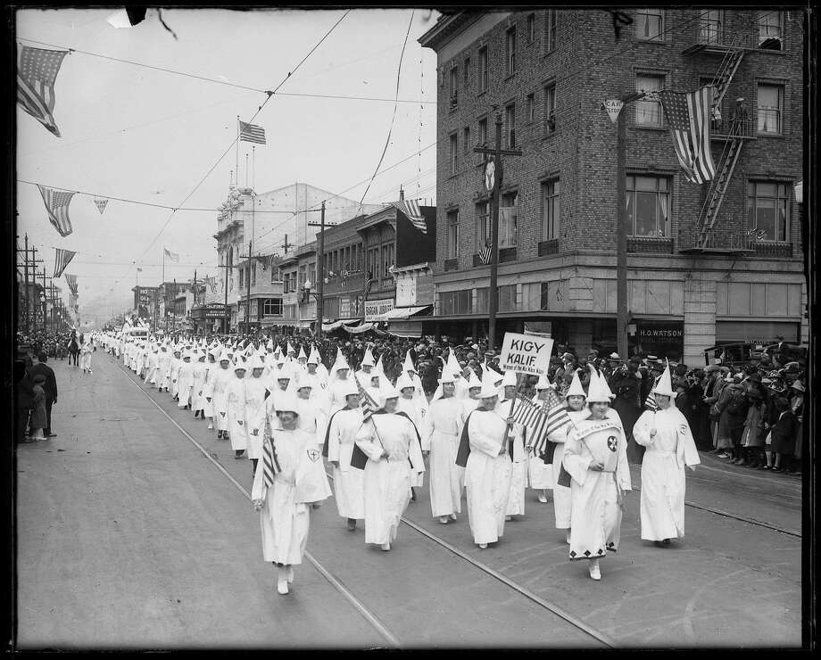 "Women of the Ku Klux Klan march in an Independence Day parade on Macdonald Avenue in downtown Richmond in 1924. In his book, ""No There There: Race, Class, and Political Community in Oakland,"" Chris Rhomberg writes that members of the Klan were scheduled to march in Oakland's July 4th parade. The city of Oakland, however, revoked their permit, prompting them to march in Richmond. ""KIGY,"" in the sign that reads ""KIGY KALIF.,"" stands for ""Klansman I Greet You."" Photo: M.L. Cohen, Gift Of Mr. Martin J. Cooney / Collection Of The Oakland Museum"