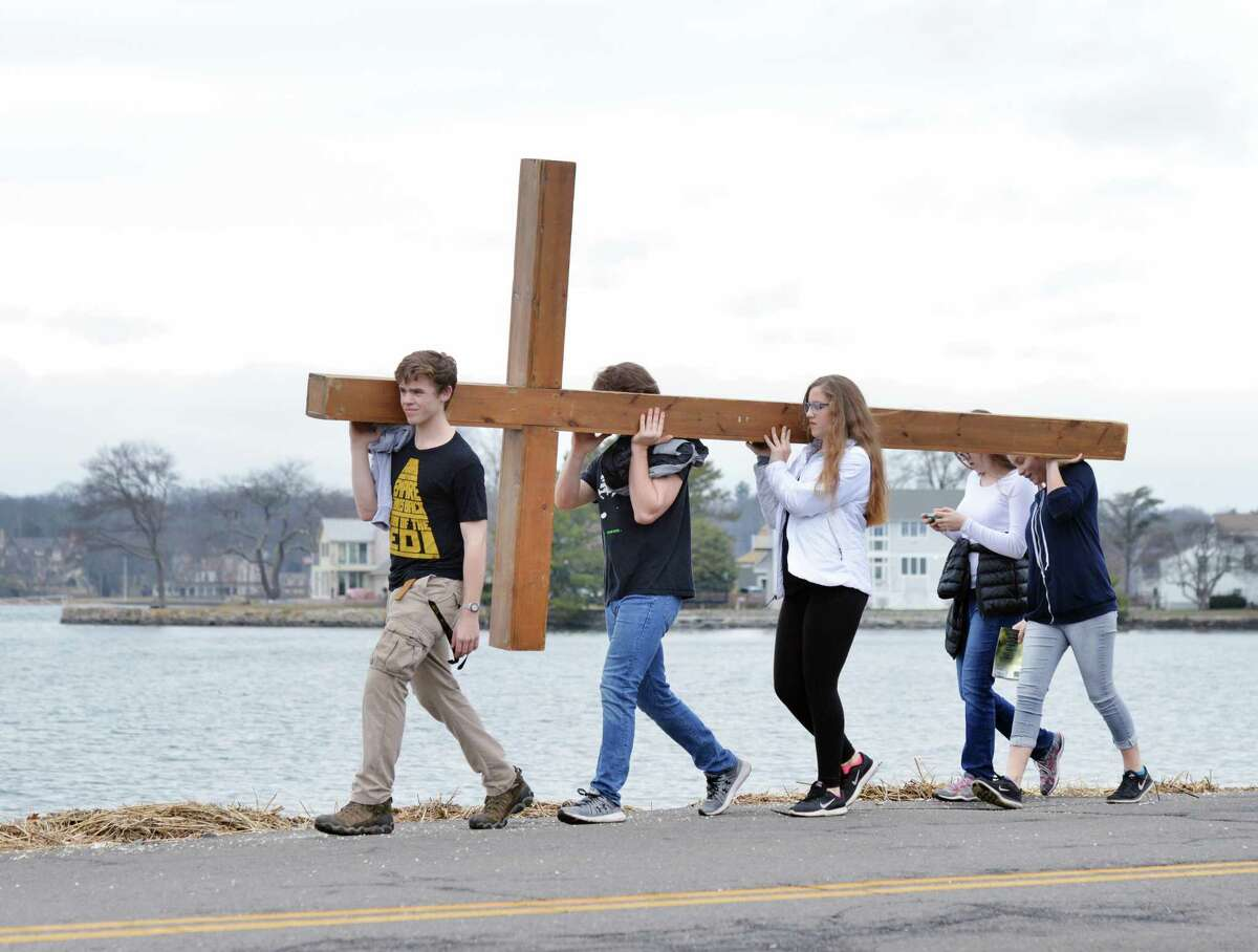 At left, Andrew Mohn, 18, of Stamford, led the First Congregational Church of Greenwich Youth Group during their annual Good Friday cross walk near Greenwich Point in Old Greenwich, Conn., Good Friday, March, 30, 2018.