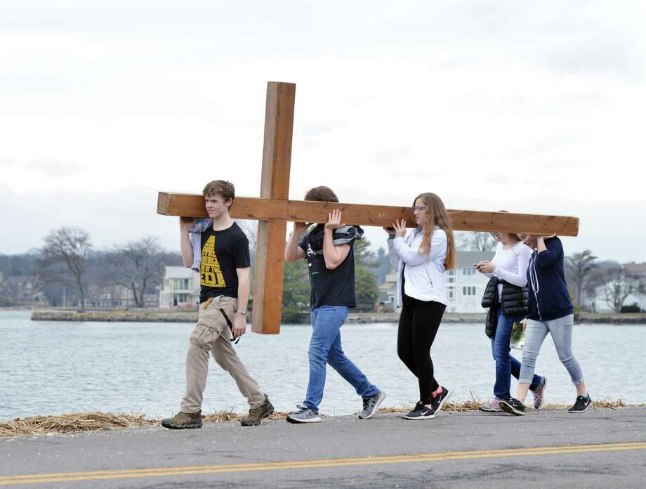 At left, Andrew Mohn, 18, of Stamford, led the First Congregational Church of Greenwich Youth Group during their annual Good Friday cross walk near Greenwich Point in Old Greenwich, Conn., Good Friday, March, 30, 2018. Photo: Bob Luckey Jr. / Hearst Connecticut Media / Greenwich Time