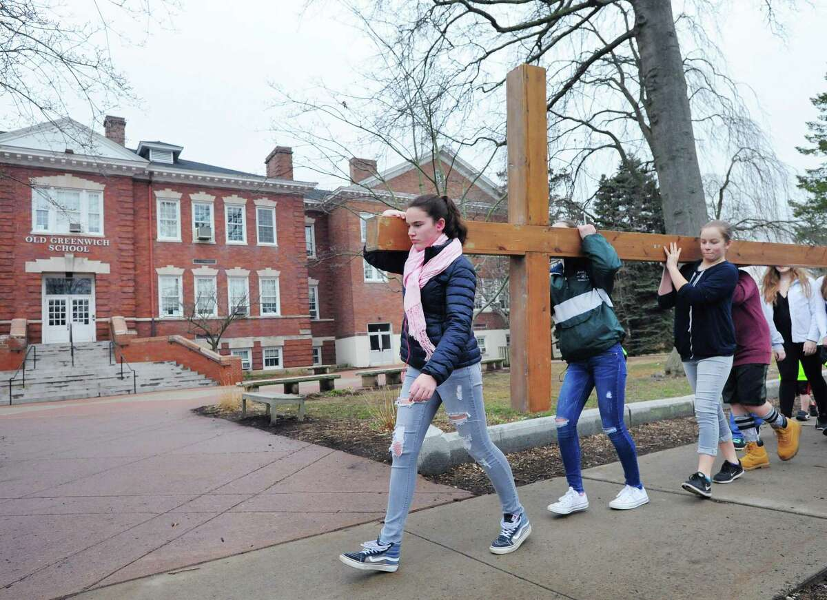 At left, Elizabeth Mohn of the First Congregational Church of Greenwich Youth Group leads the group's cross walk past the Old Greenwich School, Old Greenwich, Conn., Good Friday, March, 30, 2018.