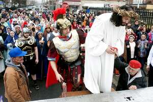 In the roll of Jesus Christ, Itamar Santos climbs onto a flatbed truck at the beginning of the annual Living Stations of the Cross procession through the streets of the East Side of Bridgeport, Conn. on Good Friday, March 30, 2018.