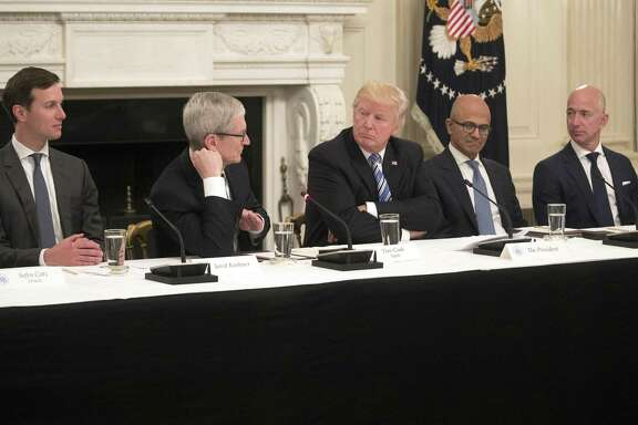 FILE-- Chief executives including Apples Tim Cook, second from left; Microsofts Satya Nadella, fourth from left; and Amazons Jeff Bezos, right, meet with President Donald Trump, center, and White House adviser Jared Kushner, left, during a roundtable discussion on technology at the White House on June 19, 2017. Once one of Trumps most vocal opponents, Silicon Valleys technology industry has increasingly found common ground with the White House.
